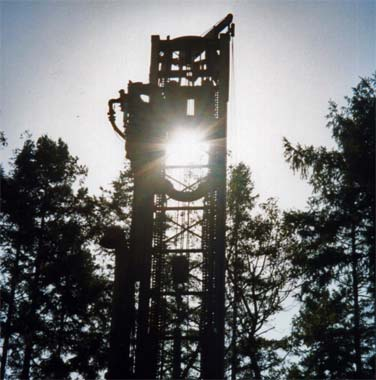 Water drilling rig backlit with sunlight